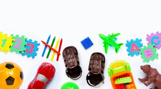 Sandalen van bruin leer voor kinderen met kleurrijk speelgoed op wit.