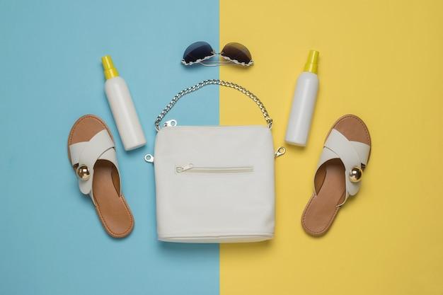 Sandalen, zonnebrandcrème en een witte tas op een gele en blauwe achtergrond. vakantieconcept. plat leggen.