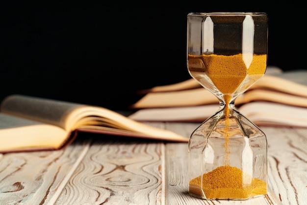 Sandglass op houten lijst met geopend boek dicht omhoog