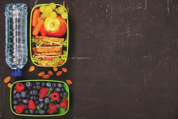 Sandwich, appel, druif, wortel, bes in plastic lunchbox en b