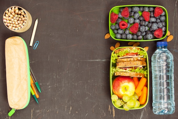 Sandwich, appel, druif, wortel, bes in plastic lunchboxen, st