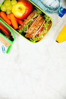 Sandwich, appel, druif, wortel, briefpapier en fles water o