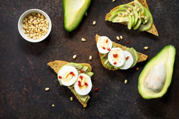 Sandwich avocado met vers gesneden avocado-ei gepocheerd en kruiden op een donkere leisteen of stenen oppervlak kopieer ruimte plat lag bovenaanzicht