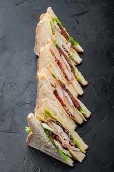 Sandwich brood tomaat, sla en gele kaas, op zwarte achtergrond