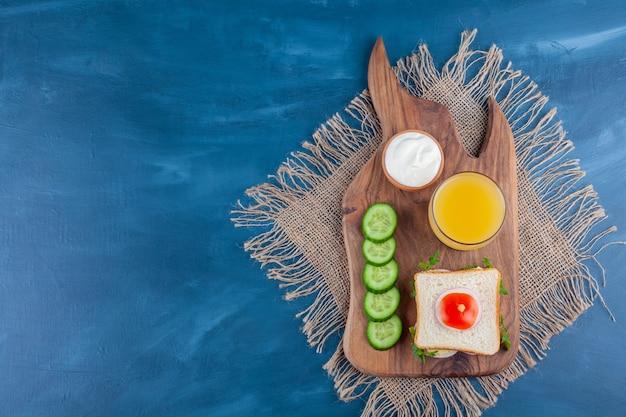 Sandwich, een glas sap, kom kaas en gesneden komkommer op een snijplank, op de blauwe achtergrond.