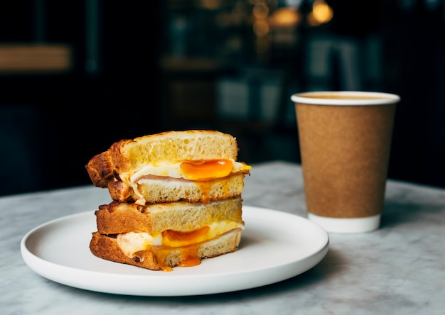 Sandwich en een kopje koffie op een tafel