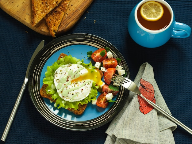 Sandwich, gepocheerd ei en salade op een donkere achtergrond