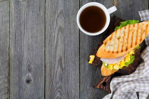 Sandwich gevuld met roerei, ham en slablaadjes achtergrond. bovenaanzicht. selectieve aandacht.