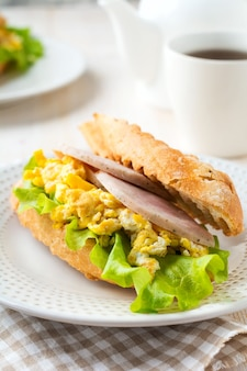 Sandwich gevuld met roerei, ham en slablaadjes