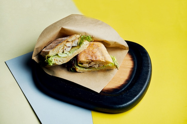 Sandwich in een ciabatta broodje met ham, tomaten, gepekelde komkommer kaas en sla op een houten dienblad. detailopname. lekker fastfood