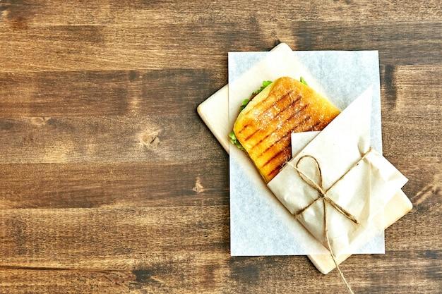 Sandwich in een envelop, vastgebonden met touw aan een houten tafel