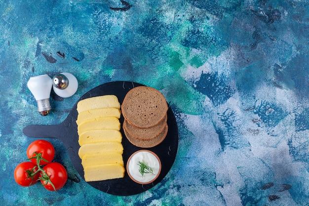Sandwich ingrediënten op een snijplank, op de blauwe achtergrond.