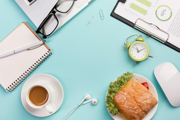 Sandwich, laptop, brillen, wekker, muis, oortelefoons op blauwe achtergrond