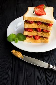 Sandwich met aardbei en pindakaas op de witte plaat