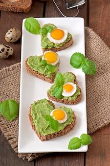 Sandwich met avocadopasta en ei in de vorm van een hart