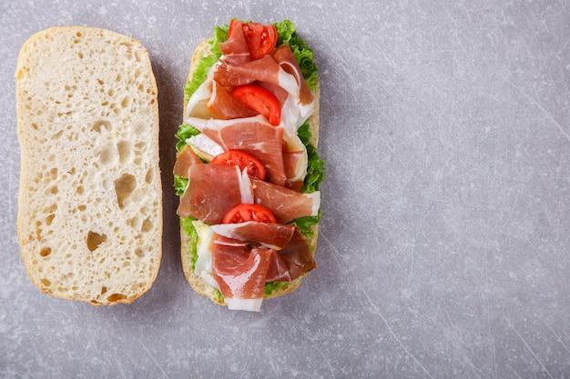 Sandwich met ciabatta, prosciutto, brie en sla