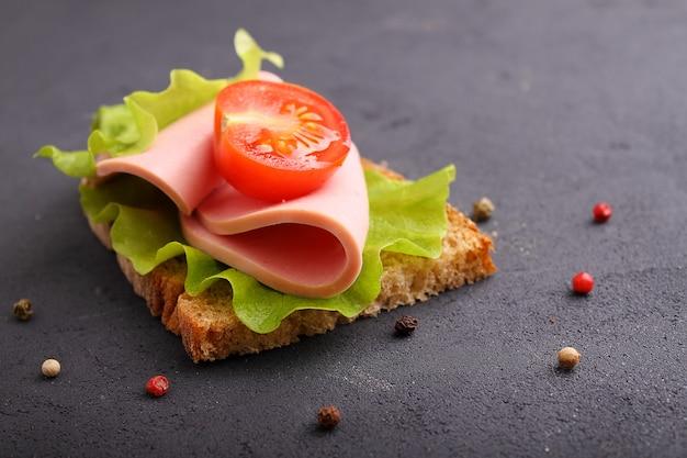 Sandwich met doctorale worst met sla en tomaat. zwarte bakground