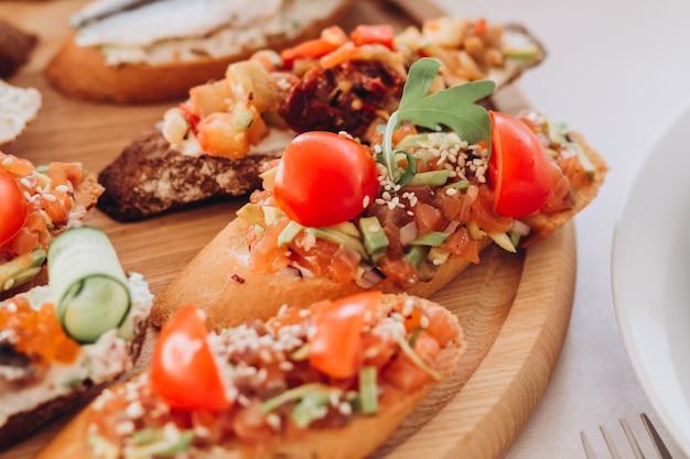 Sandwich met forel, cherrytomaatjes en sla. plaat van snacks.