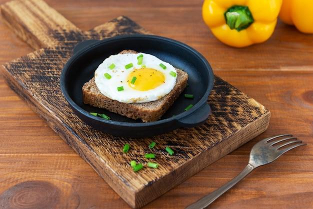 Sandwich met gebakken eieren met groene uien en kruiden in een gietijzeren pan