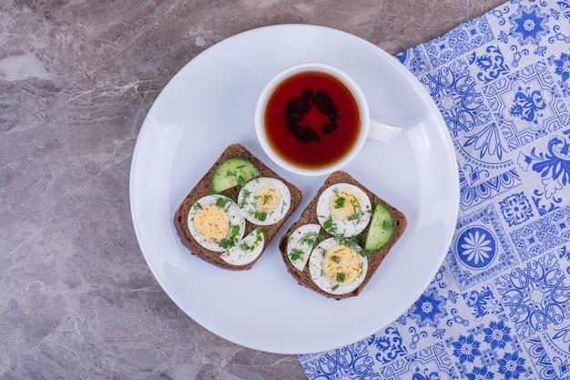 Sandwich met gekookt ei met een kopje thee in een witte plaat.