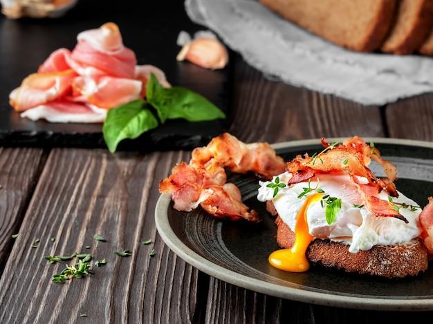 Sandwich met gepocheerd ei, gebakken ham en roomkaas, gegarneerd met microgreens