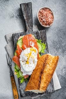 Sandwich met gepocheerd ei, gerookte zalm en avocado op toast. witte tafel. bovenaanzicht.