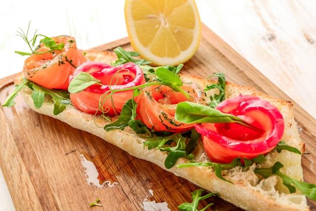Sandwich met geroosterd brood en zalm op een houten tafel