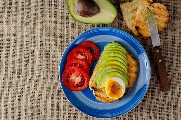 Sandwich met gesneden avocado, zacht gekookt ei en tomaten op zakken. evenwichtige voeding bovenaanzicht. geïsoleerd op wit