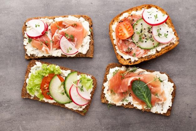 Sandwich met granenbrood en salami op donker marmer.