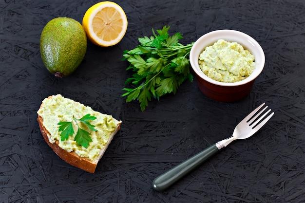 Sandwich met guacamole. citroen, avacadopeterselie op een zwarte achtergrond