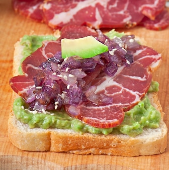 Sandwich met ham, avocadosaus en gekarameliseerde uien