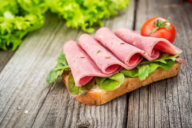 Sandwich met ham en groenten. biologische producten op een houten tafel