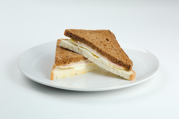 Sandwich met ham en kaas in witte geïsoleerde plaat. clubsandwich met verschillende broodclose-up