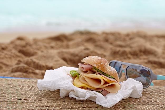 Sandwich met ham en kaas op een strand
