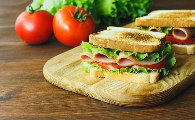 Sandwich met ham groene sla en tomaat op een houten bruin keukenbord