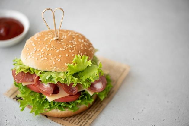 Sandwich met ham, maasdam kaas, tomaten en groene salade op een witte tafel