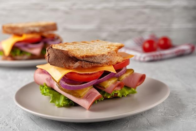 Sandwich met ham, tomaten, sla en gele kaas op een grijze achtergrond