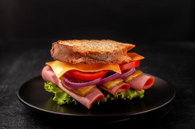 Sandwich met ham, tomaten, sla en gele kaas op een zwarte achtergrond