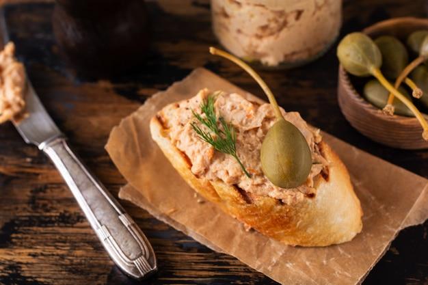 Sandwich met heerlijke zelfgemaakte kippenpastei met kruiden en dille in een glazen pot en een sneetje brood in de buurt en kappertjes geserveerd in vintage stijl op oud bord en tafel. selectieve aandacht.