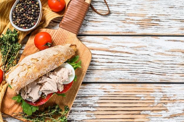 Sandwich met huisgemaakte leverpastei, rucola, tomaat, ei en kruiden