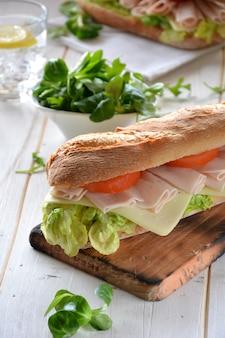 Sandwich met kaas en kalkoenham geserveerd met sla en tomaat