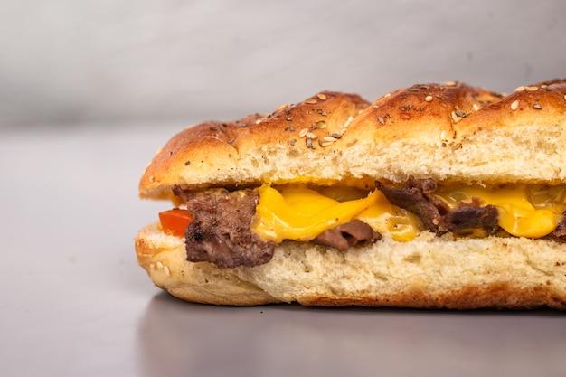 Sandwich met kaas in een vers brood op een grijze ondergrond.