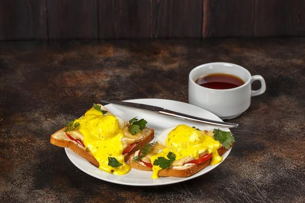 Sandwich met kaas, spek, tomaat en gepocheerd ei op plaat