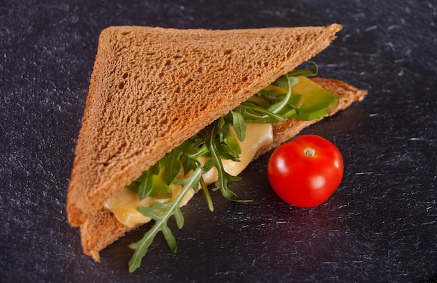 Sandwich met kalkoenfilet, kaas, sla, rucola, tomaten en ui op een zwarte plaat