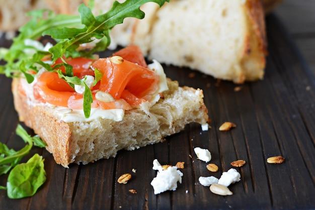Sandwich met licht gezouten zalm, rucola, zaden en kwark op het bord. zuurdesembrood toast met gezouten vis, smorrebrod.