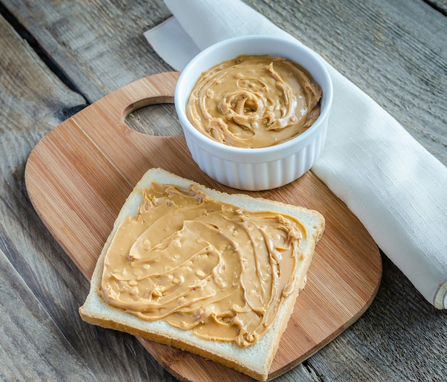 Sandwich met pindakaas op het houten bord
