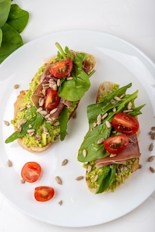 Sandwich met prosciutto, jamon, tomaten en avocado