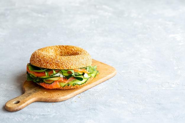 Sandwich met rode vis op het bord. juiste voeding. rode vis. het maken van een sandwich .burger met vis. cheeseburger met rode vis. lekkere lunch. heerlijke hamburger zonder vlees. een plek voor copywriting
