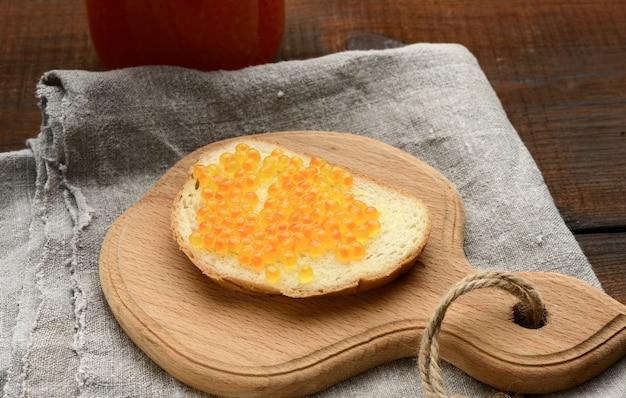 Sandwich met rode zalmkaviaar op een houten bord