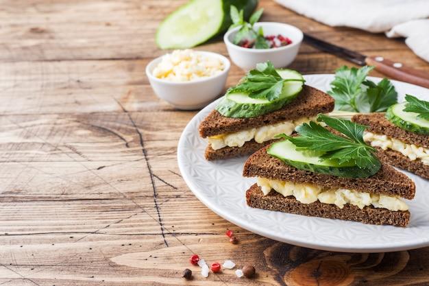 Sandwich met roerei en komkommers op houten rustieke achtergrond